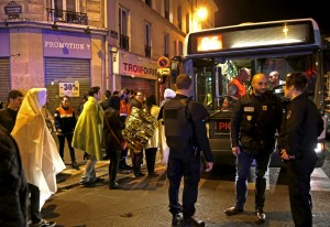 French police stand near people warming up on a street before being evacuated by bus near the Bataclan concert hall following fatal attacks in Paris, France