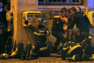 French fire brigade members aid an injured individual near the Bataclan concert hall following fatal shootings in Paris, France